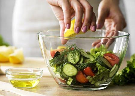 Mão de mulher espremendo limão em salada