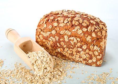 Pão de aveia sobre a mesa com colher cheia de aveia
