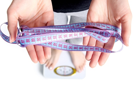 Pessoa em cima da balança segurando fita métrica com as mãos
