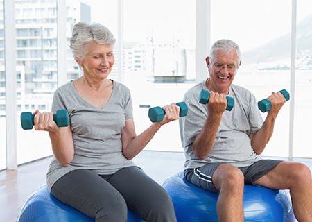 Idosos se exercitando em bolas de pilates, segurando halteres