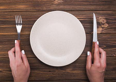 Mãos segurando talheres ao lado de prato vazio sobre a mesa