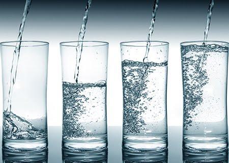 Copos com níveis diferentes de água em cima da mesa