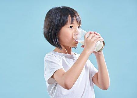 Menina bebendo copo de leite