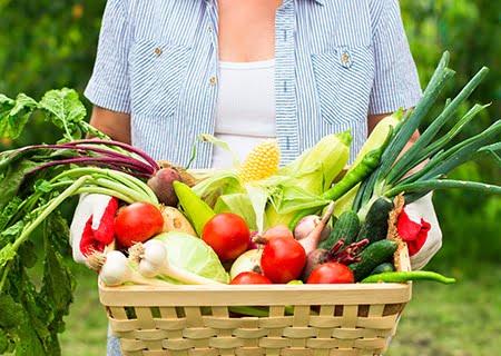 Mulher segurando cesta de verduras e legumes