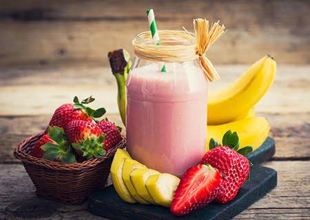 Copo com vitamina de morango sendo servida, com bananas e morangos