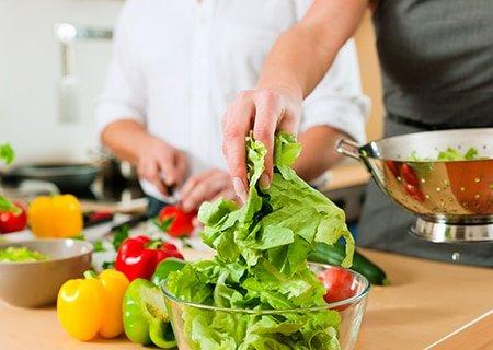 Verduras e legumes em bowls e mãos os manuseando