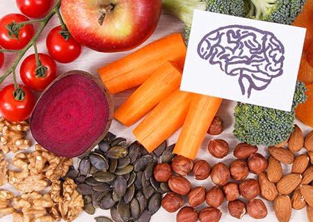 Mesa com alimentos como cenouras, maçã e nozes, e papel com desenho de cérebro ao lado