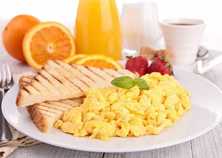 Pão com ovos mexidos e fatias de pão e, ao fundo, copos com suco de laranja e leite; uma mesa de café da manhã
