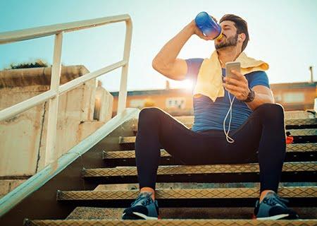 Homem vestido com roupas de ginástica sentado em escada tomando água em uma squeeze