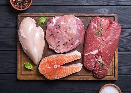 Vários tipos de carne sobre tábua, bovina, de frango e de peixe