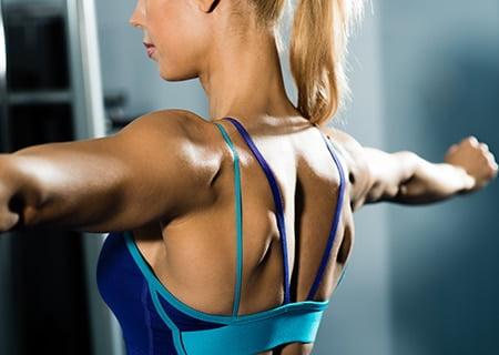 Mulher de costas treinando musculação