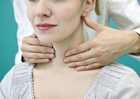 Mulher sentada e médico atrás apalpando seu pescoço para verificar a tireoide