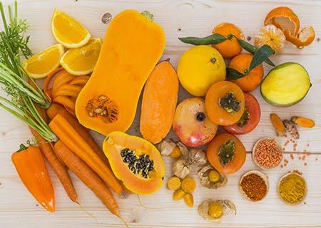 Alimentos alaranjados sobre a mesa, como cenouras, mamão e caquis