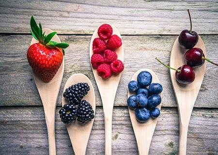 5 colheres de pau sobre a mesa, cada uma com um tipo de fruta vermelha, como morango e amora