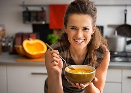 Mulher feliz com bowl de comida na mão
