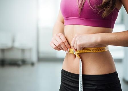 Mulher medindo cintura com fita métrica