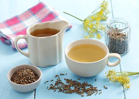 Canecas brancas com chá de erva-doce em cima de mesa