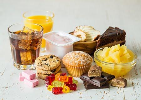 Mesa com diversos alimentos ricos em açúcar, como bolos, pedaços de gelatina, bolachas, chocolates e sucos
