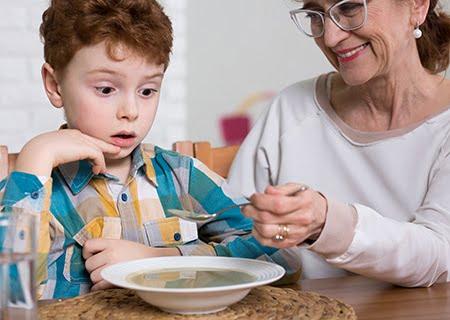 Mãe alimentando o filho com sopa