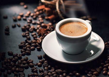 Xícara de café em cima de mesa com grãos de café ao lado