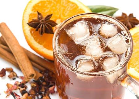 Copo com chá-mate e gelo, ao lado de uma laranja fatiada e pedaços de canela