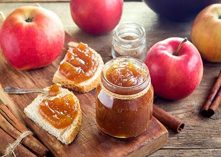 Tábua com geleia de maçã em pote, em torradas e maçãs em volta
