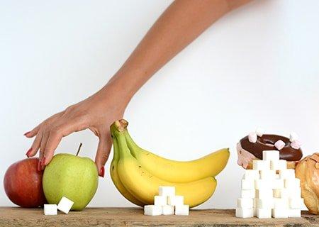 Mesa com pera, banana e rosquinhas e cubinhos de açúcar em frente cada um deles, indicando a quantidade de açúcar que contém. Mão feminina pegando a pêra.