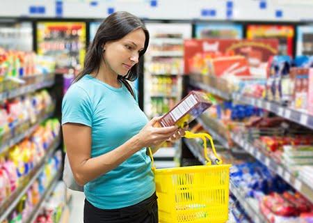 Mulher no supermercado segurando uma caixa de alimento e lendo o rótulo