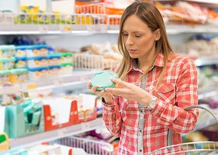 Mulher no supermercado lendo rótulo de alimento