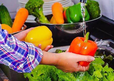 Mão feminina lavando verduras