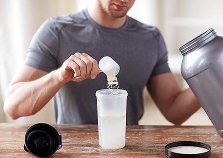 Homem colocando suplemento em copo