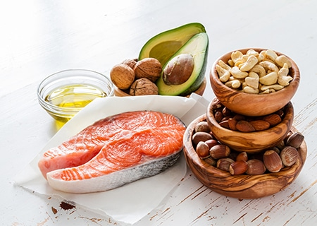 Mesa com oleaginosas, abacate, salmão e azeite