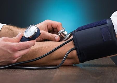 Mãos de médico e paciente, o primeiro mede a pressão do segundo com aparelho