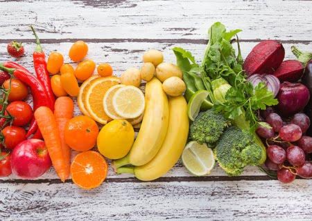 Mesa com laranjas, cenouras, folhas, batatas etc.