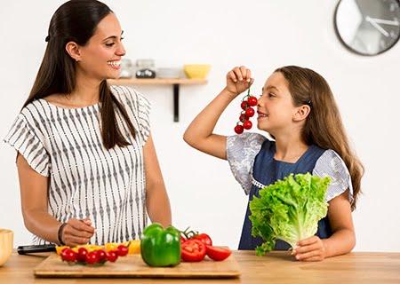 Mulher e garotinha atrás de bancada repleta de verduras na cozinha, se olhando e sorrindo. Garota segurando um pé de alface e tomates com as mãos.