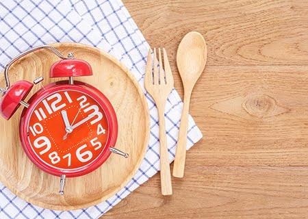 Mesa com toalha xadrez, talheres e prato sob relógio