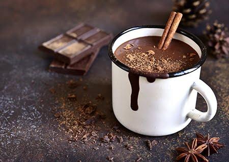 Caneca branca com chocolate quente em cima da mesa