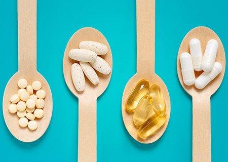 Mesa com colheres de pau com pílulas de suplementos