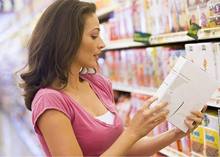 """Uma mulher em um supermercado lendo o rótulo de um produto, representando o cuidado com a verificação das informações dos produtos que contém o selo """"zero gordura trans"""""""