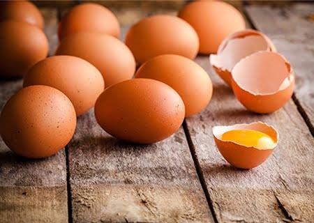 Imagem com vários ovos em uma superfície de madeira, com um deles quebrado