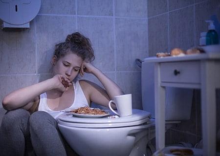 Mulher no banheiro comendo, com cara de preocupada