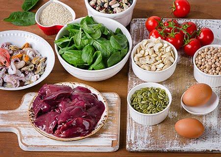 Mesa com diversos alimentos em cumbucas, como carnes, frutos do mar, ovos e oleaginosas
