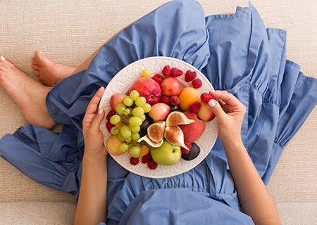 Mulher sentada, com um prato repleto de diferentes frutas no seu colo