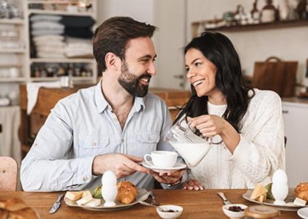 Casal sentado à mesa com alimentos. Mulher serve leite ao homem e os dois se olham, sorrindo