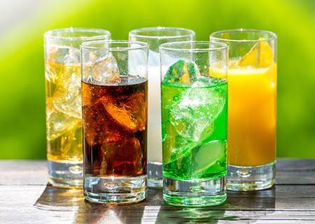 Mesa com diversos copos de refrigerante, como de cola e limão, e suco