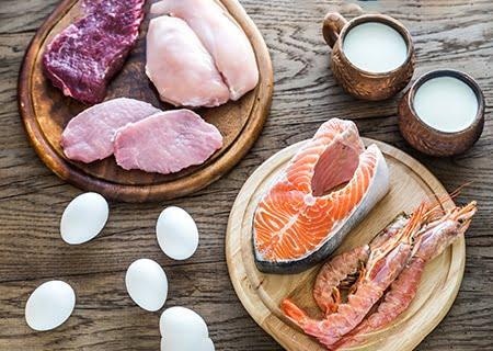 Mesa com ovos, xícaras com leite, peixes e carnes