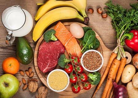 Mesa com diversos vegetais, peixes, ovos e carnes