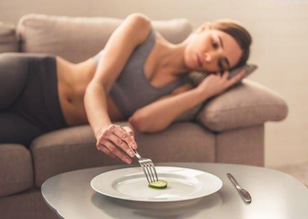Mulher deitada no sofá com expressão triste dando garfada em um prato que contém apenas um pequeno pedaço de legume