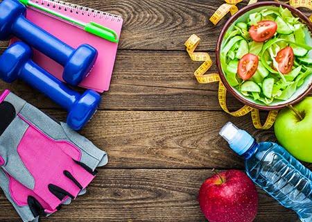 Sobre uma mesa, do lado esquerdo, halteres e luvas para musculação; e, do lado direito, água, maçã, prato de salada e fita métrica