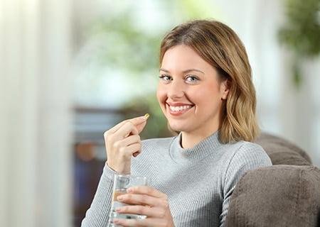 Mulher segurando pílula com uma mão e copo de água na outra